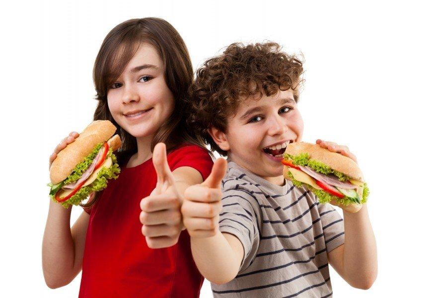 Kids eating big sandwich showing OK sign