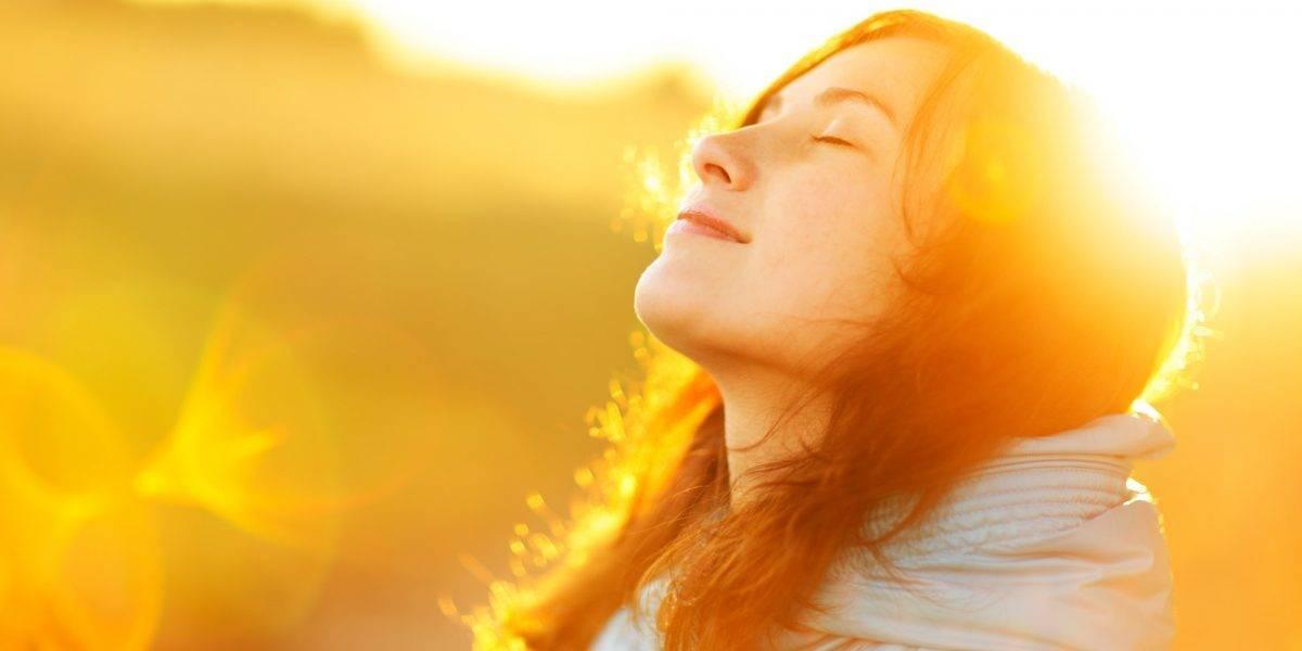mujer con la cara iluminada por el sol